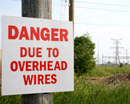 Warning sign that says Danger due to overhead wires